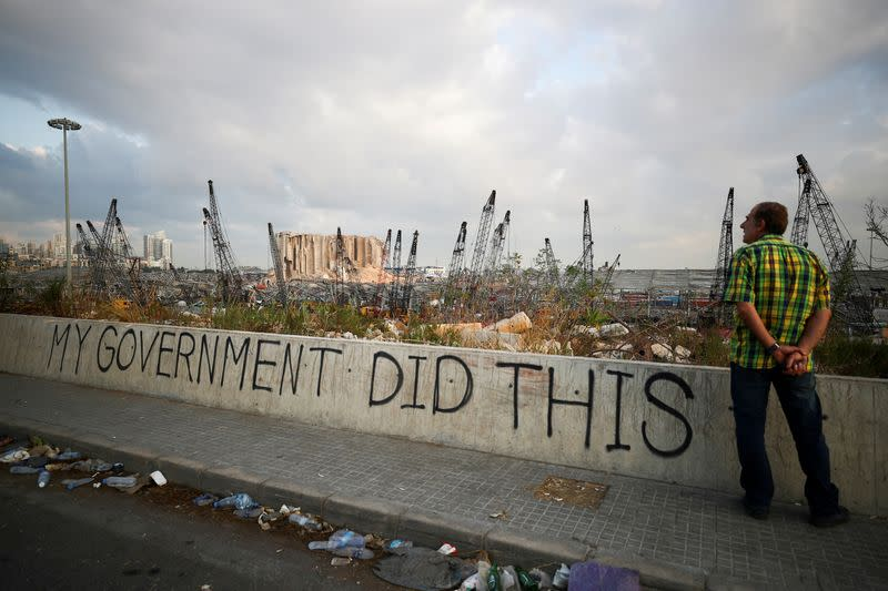 FILE PHOTO: A man stands next to graffiti at the damaged port area in the aftermath of a massive explosion in Beirut