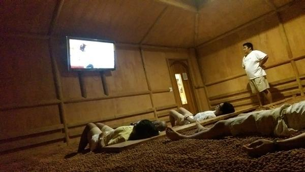 Room with stone floors, with pebbles and people lying down watching television