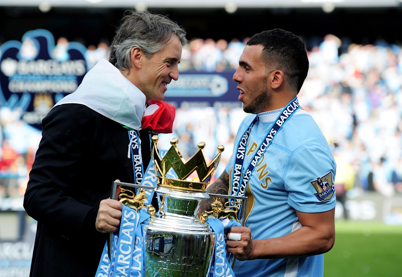 MANCHESTER, ENGLAND - MAY 13:  (L-R) Roberto Mancini the manager of Manchester City and Carlos Tevez of Manchester City celebrate with the trophy following the Barclays Premier League match between Manchester City and Queens Park Rangers at the Etihad Stadium on May 13, 2012 in Manchester, England.  (Photo by Shaun Botterill/Getty Images)