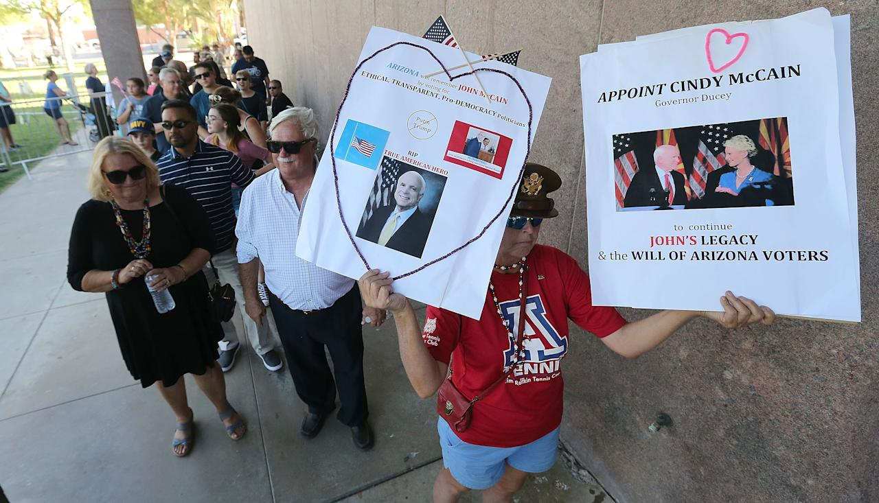 <p>Cindy O'Neil of Tucson, Arizona (R) holds up signs as she and others wait in line for the public viewing of the late Sen. John McCain as his body lies in state at the Arizona State Capitol Rotunda on Aug. 29, 2018 in Phoenix, Ariz. (Photo: Ralph Freso/Getty Images) </p>