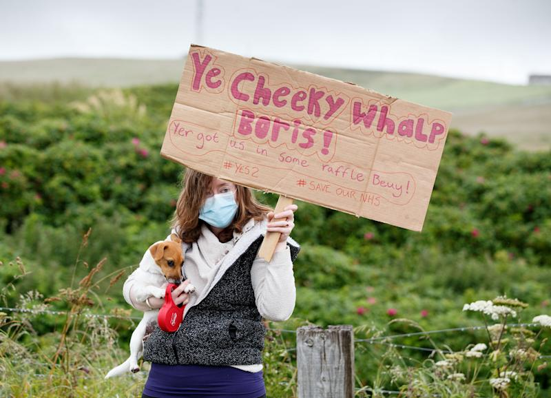 STROMNESS, SCOTLAND - JULY 23: A protester holds her dog and a sign as a group of demonstrators gather to greet British Prime Minister Boris Johnson as he visits the Orkney Islands on July 23, 2020 in Stromness, Scotland. This week marks one year as U.K. Prime Minister for Conservative Party leader Boris Johnson. Today he is visiting businesses in the Orkney Islands in Scotland to reaffirm his commitment to supporting all parts of the UK through the Coronavirus pandemic. Later he will visit a military base in Moray to thank Military personnel for their service. (Photo by Robert Perry/Getty Images)