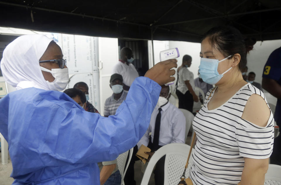 A nurse in protective gear takes the temperature of a woman waiting to take the Moderna coronavirus vaccine at the health center in Lagos, Nigeria Wednesday, Aug. 25, 2021. Nigeria has begun the second rollout of COVID-19 vaccines as it aims to protect its population of more than 200 million amid an infection surge in a third wave of the pandemic. (AP Photo/Sunday Alamba)