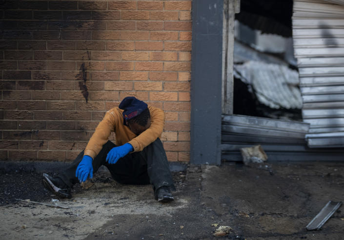 A family member is emotional after police officers removed the body his brother who was found inside a burned shop in Johannesburg, South Africa, Sunday, July 11, 2021. Protests have spread from the KwaZulu Natal province to Johannesburg against the imprisonment of former South African President Jacob Zuma who was imprisoned last week for contempt of court. (AP Photo/Themba Hadebe)