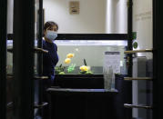 A staff member waits for customers at a window set up to sell takeaway food at a restaurant in Prague, Czech Republic, Wednesday, Oct. 14, 2020. The Czech Republic has imposed a new series of restrictive measures in response to a record surge in coronavirus infections. Starting Wednesdays all bars and restaurants can only sell takeaway while drinking of alcohol is banned at public places. (AP Photo/Petr David Josek)
