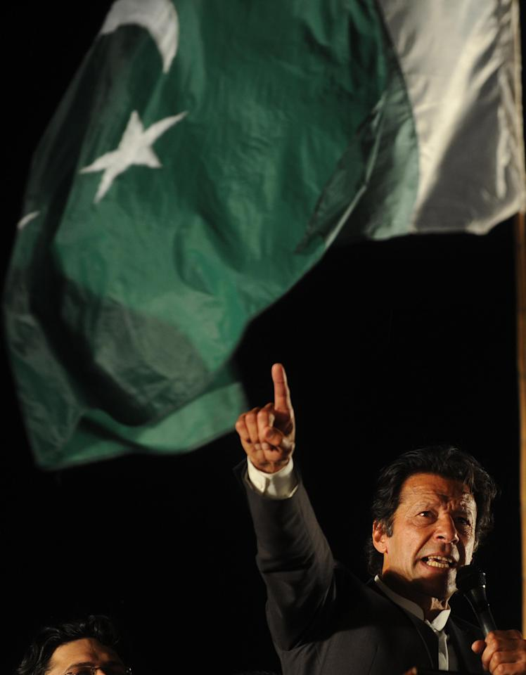 Former cricketer and chairman of Pakistan's political party Pakistan Tehreek-e-Insaf Imran Khan gestures as he addressing a public meeting in Lahore on March 23, 2013. Cricket legend Imran Khan is expected to unveil his manifesto to become Pakistan's next prime minister at an election rally on Saturday, where turnout will be a key test for his chances of success.  AFP PHOTO/Arif ALI
