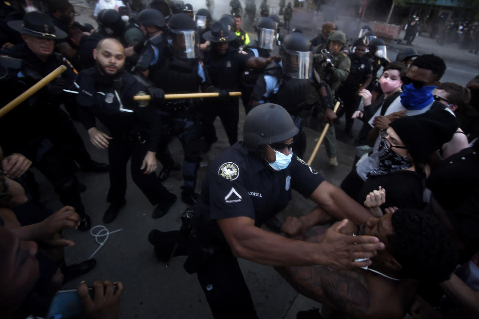Police officers and protesters clash in Atlanta on May 29, 2020, during a protest in response to George Floyd's death in police custody in Minneapolis. (AP Photo/Mike Stewart)