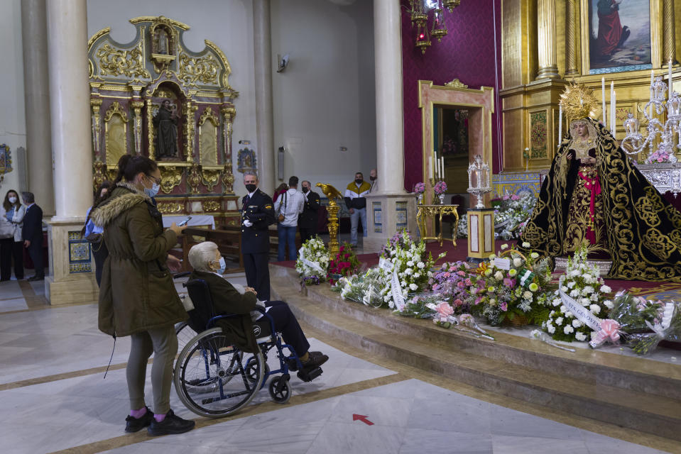 Catholic worshipers pay respects to a figure of Virgin Mary inside El Cerro church during the Holy Week in Seville, southern Spain, Tuesday, March 30, 2021. Few Catholics in devout southern Spain would have imagined an April without the pomp and ceremony of Holy Week processions. With the coronavirus pandemic unremitting, they will miss them for a second year. (AP Photo/Laura Leon)