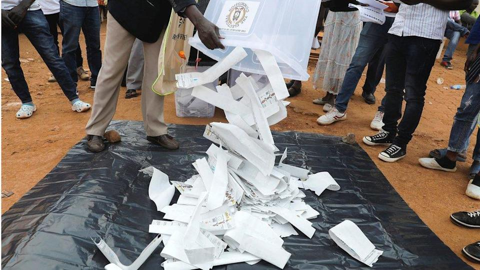 Election officials empty a ballot box to count votes after polling stations closed in elections in Kampala, Uganda - 14 January 2021