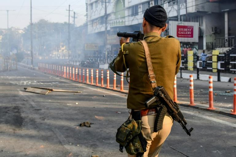 A security officer fires tear gas during a curfew in Guwahati, Assam on December 12, 2019 (AFP Photo/Biju BORO)