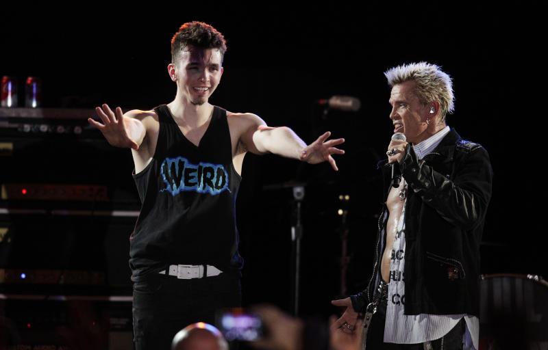 Billy Idol, right, is joined on stage by an emotional Michael Henrichsen, left, as Idol performs Friday, Oct. 26, 2012, in Seattle. Idol came to play in Seattle after Henrichsen launched a two-year grass-roots campaign to convince the rock star to play for his birthday party. (AP Photo/Ted S. Warren)