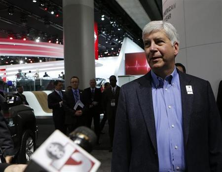 Michigan Governor Snyder is interviewed as he tours the display floor during the press preview day of the North American International Auto Show in Detroit