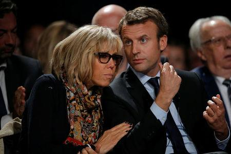 FILE PHOTO: Former French economy minister Emmanuel Macron (R) and his wife Brigitte Trogneux attend a political rally for his political movement, En Marche !, or Forward !, in Le Mans, France, October 11, 2016. REUTERS/Stephane Mahe/File Photo