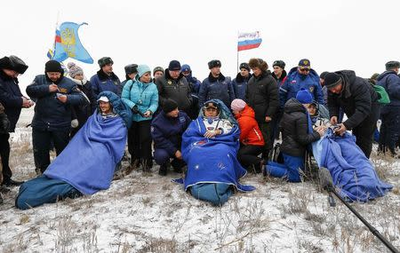 The International Space Station (ISS) crew of Alexander Gerst of Germany (L-R), Maxim Surayev of Russia and Reid Wiseman of the U.S. rest after landing in a remote area near the town of Arkalyk in northern Kazakhstan, November 10, 2014. REUTERS/Shamil Zhumatov