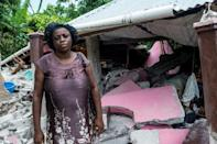 A woman in front of her home, devastated by Saturday's earthquake, in Camp Perrin, in Haïti, le 16 août 2021