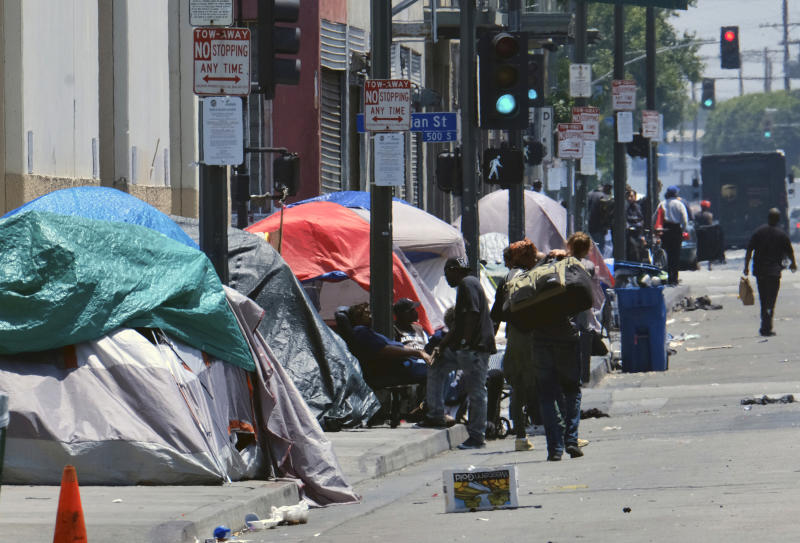 FILE - In this May 30, 2019 file photo, tents housing homeless line a street in downtown Los Angeles. The Los Angeles Homeless Services Authority has failed to meet goals for placing people into permanent housing and for referring them to substance abuse and mental health treatment, according to a city audit released Wednesday, Aug. 28, 2019. (AP Photo/Richard Vogel,File)