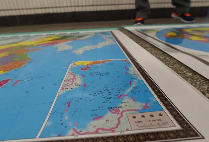 In this photo taken on June 15, 2016 a vendor stands behind a map of China including an insert with red dotted lines showing China's claimed territory in the South China Sea (AFP Photo/GREG BAKER)