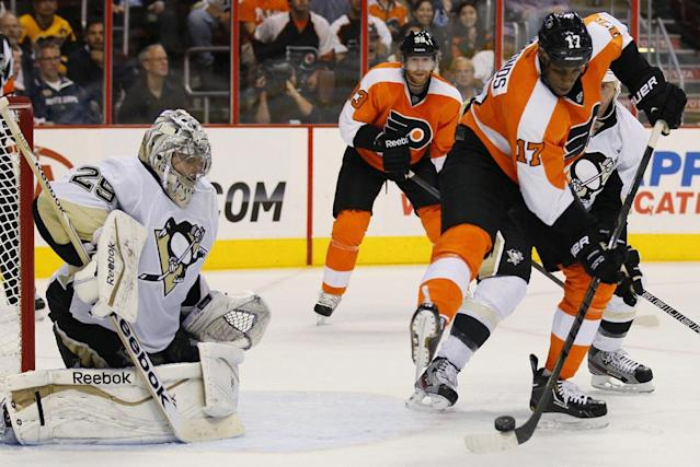 Philadelphia Flyers' Wayne Simmonds, right, directs the puck toward Pittsburgh Penguins goalie Marc-Andre Fleury for a tip-in goal with 2 seconds remaining in the second period of an NHL hockey game, Thursday, Oct. 17, 2013, in Philadelphia. (AP Photo/Tom Mihalek)