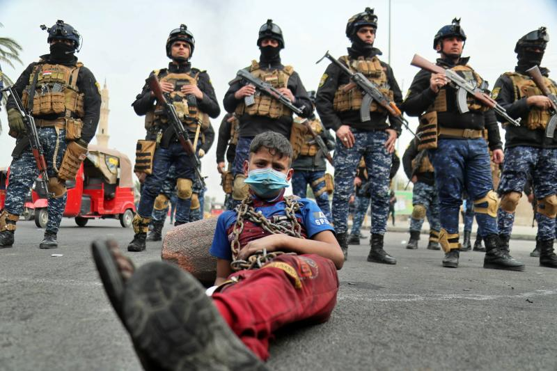 Anti-government protesters stage a sit-in while security forces stand guard during ongoing protests in downtown Baghdad, Iraq, Sunday, Jan. 19, 2020. Black smoke filled the air as protesters burned tires to block main roads in the Iraqi capital Baghdad, expressing their anger at poor services and shortages despite religious and political leaders calling for calm. (AP Photo/Hadi Mizban)