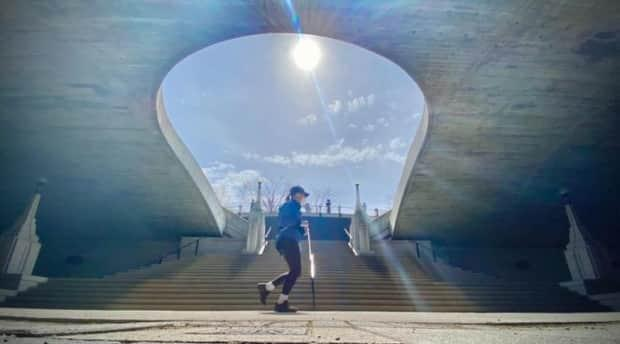 A runner in a mask passes underneath the downtown Ottawa bridge connecting Rideau and Wellington streets on April 27, 2021. (Christian Patry/Radio-Canada - image credit)