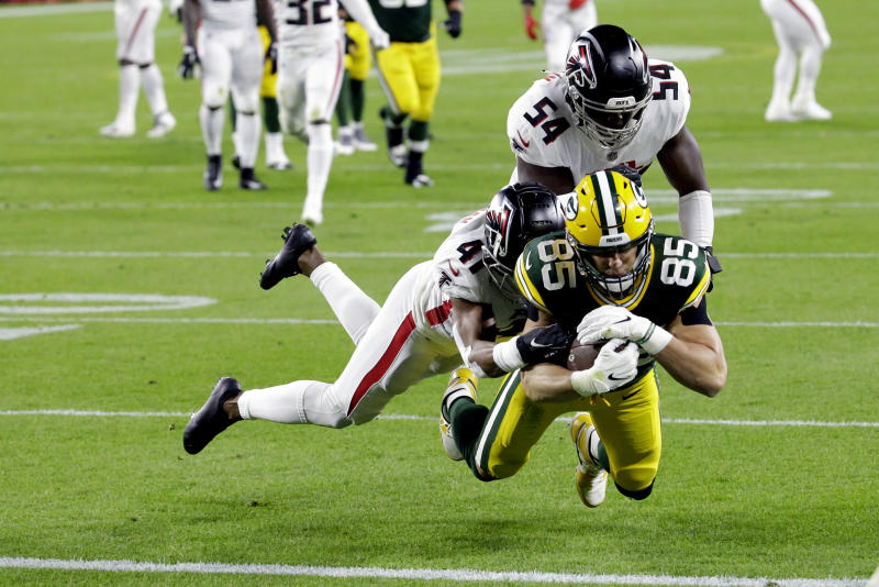 Green Bay Packers' Robert Tonyan (85) goes in for a touchdown as he is tackled by Atlanta Falcons' Sharrod Neasman (41) and Foye Oluokun (54). (AP Photo/Mike Roemer)