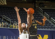Michigan center Hunter Dickinson (1) defends Oakland forward Daniel Oladapo (4) going to the basket, in the first half of an NCAA college basketball game at Crisler Center in Ann Arbor, Mich., Sunday, Nov. 29, 2020. (AP Photo/Tony Ding)
