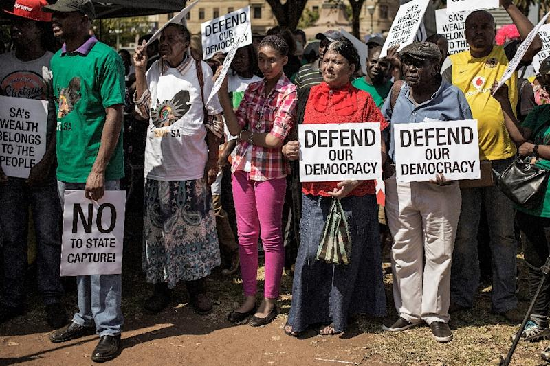 People hold placards during a rally outside the South African National Treasury to protest against President Jacob Zuma in Pretoria on April 3, 2017