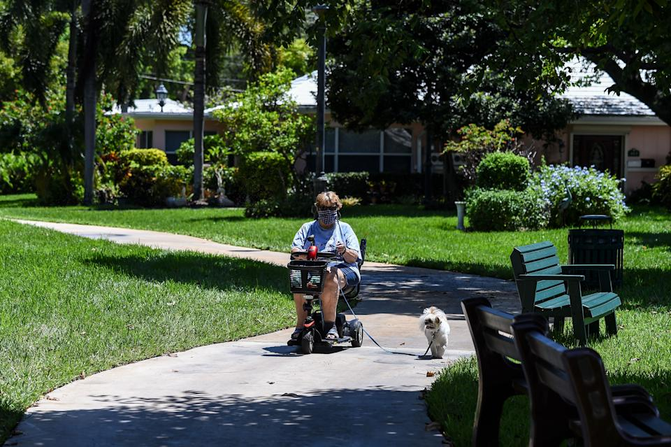 An elderly woman on an electric scooter walks her dog in the garden of John Knox Village, a retirement community in Pompano Beach some 40 miles north of Miami, Florida on August 7, 2020. - About 900 retirees live in the John Knox Village senior community in Pompano Beach, South Florida. Of these, about 400 have learned to use technology to order food to their apartments, communicate with each other or participate in online social activities. Thirty of them participate in a book club over Zoom since the pandemic began. Florida, a coronavirus hotspot with nearly 8,000 deaths, is the US state with the highest proportion of elderly people, which is also the population most vulnerable to the disease. 20% of its 21 million inhabitants are over 65, according to a 2019 Population Reference Bureau study. (Photo by CHANDAN KHANNA / AFP) (Photo by CHANDAN KHANNA/AFP via Getty Images)