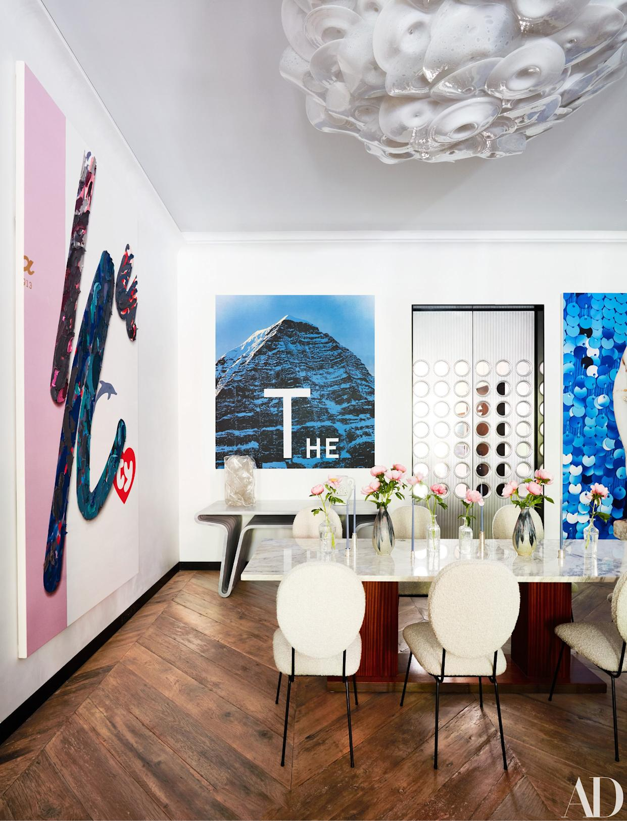 """<div class=""""caption""""> Lighting by Jeff Zimmerman hangs above the vintage Rene-Jean Caillette dining table and Joaquim Tenreiro chairs. Paintings by Laura Owens (left) and Ed Ruscha. </div>"""