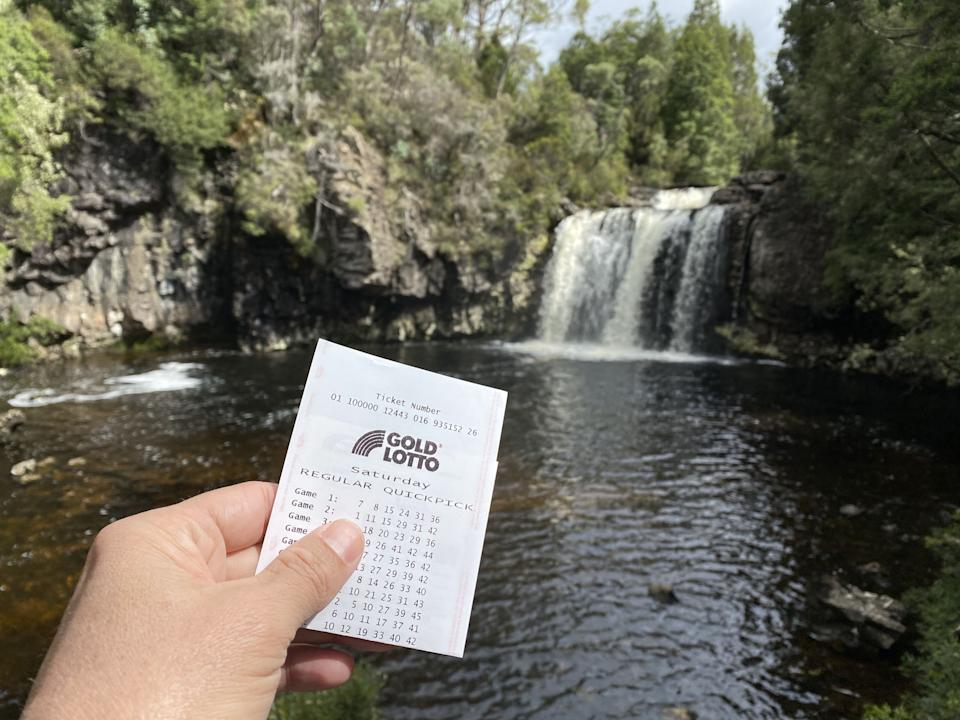 Person holding Lotto ticket in front of Australian waterfall. Source: The Lott