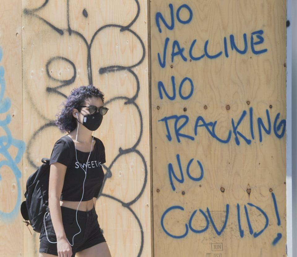 "<span class=""caption"">A woman walks by graffiti reading 'No vaccine, No tracking, No COVID', in Montréal on Aug. 16, 2020. </span> <span class=""attribution""><span class=""source"">THE CANADIAN PRESS/Graham Hughes</span></span>"
