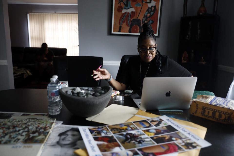 Kimberly Ross-Holmes works on her laptop at her home in Evanston, Friday, April 23, 2021. The Chicago suburb will become the first to pay reparations in the form of housing grants. She said she is glad that Juneteenth will be a federal holiday, but hopes that the federal government takes up more issues that affect the everyday lives of Black people. (AP Photo/Shafkat Anowar)