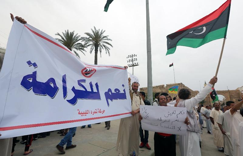 "Libyans hold a banner reading ""Yes to dignity"" during a demonstration to support ""Operation Dignity"" on May 23, 2014 in Tripoli, the operation was launched by general Haftar, who started his career under Moamer Kadhafi (AFP Photo/Mahmud Turkia)"