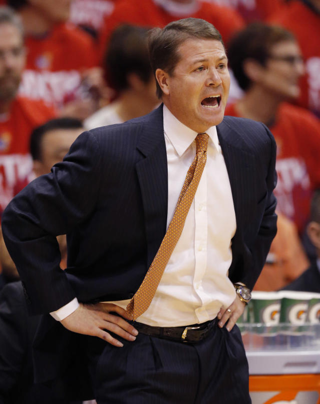 Oklahoma State head coach Travis Ford yells to his team during the first half of an NCAA college basketball game against Kansas at Allen Fieldhouse in Lawrence, Kan., Saturday, Jan. 18, 2014. (AP Photo/Orlin Wagner)
