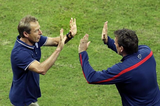 United States' head coach Juergen Klinsmann celebrates with a staff member after Jermaine Jones scored his side's first goal during the group G World Cup soccer match between the USA and Portugal at the Arena da Amazonia in Manaus, Brazil, Sunday, June 22, 2014. (AP Photo/Themba Hadebe)