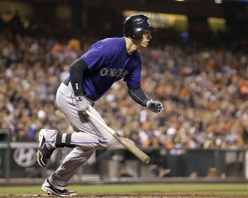 Colorado Rockies' Tyler Colvin heads to first on an RBI single against the San Francisco Giants during the fourth inning of a baseball game in San Francisco, Friday, Aug. 10, 2012. (AP Photo/Tony Avelar)