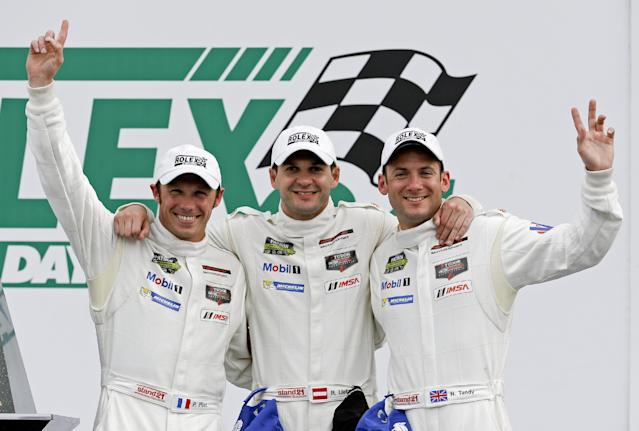 Porsche North American team drivers, from left, Patrick Pilet, of France, Richard Lietz, of Austria and Nick Tandy, of England, celebrate after winning the GT LeMans Class in the IMSA Series Rolex 24 hour auto race at Daytona International Speedway in Daytona Beach, Fla., Sunday, Jan. 26, 2014.(AP Photo/John Raoux)