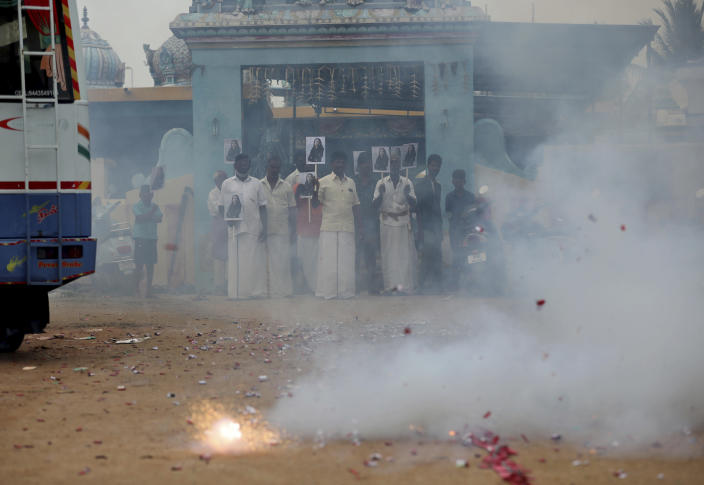 Villagers burst firecrackers and hold placards featuring U.S. Vice President-elect Kamala Harris ahead of her inauguration, in Thulasendrapuram, the hometown of Harris' maternal grandfather, south of Chennai, Tamil Nadu state, India, Wednesday, Jan. 20, 2021. A tiny, lush-green Indian village surrounded by rice paddy fields was beaming with joy Wednesday hours before its descendant, Kamala Harris, takes her oath of office and becomes the U.S. vice president. (AP Photo/Aijaz Rahi)