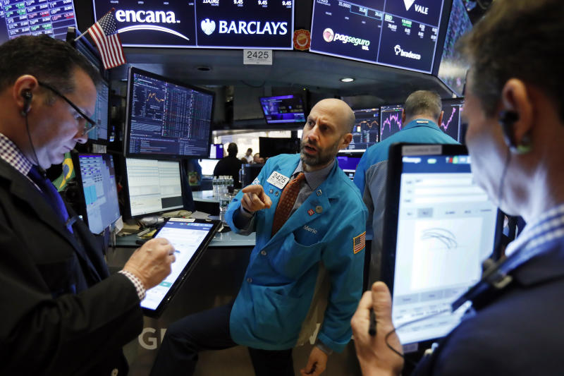 FILE - In this Jan. 10, 2020, file photo specialist Meric Greenbaum, center, works at his post on the floor of the New York Stock Exchange. The U.S. stock market opens at 9:30 a.m. EST on Thursday, Jan. 16. (AP Photo/Richard Drew, File)