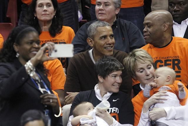 "A woman makes a ""selfie"" with U.S. President Barack Obama (C) at the game between Princeton and Green Bay for the 2015 Women's NCAA Basketball Tournament at the XFINITY Center in College Park, Maryland March 21, 2015. Obama's niece Leslie Robinson plays for Princeton. REUTERS/Yuri Gripas"