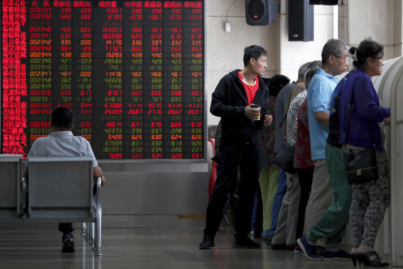 In this Thursday, Sept. 19, 2019, photo, Chinese investors check stock prices at a brokerage house in Beijing. Asian shares were mostly higher on Friday, Sept. 20, 2019 after a lackluster session on Wall Street, as investors shifted their focus to China-U.S. trade talks after a busy week of central bank news. (AP Photo/Andy Wong)