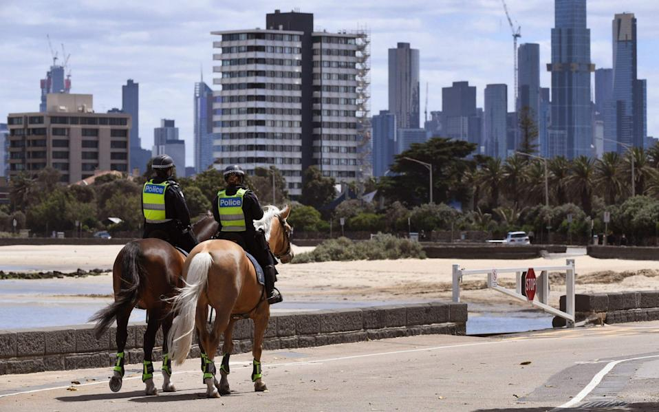 Police patrol on the St Kilda esplanade in Melbourne as the city exits lockdown after more than 100 days - AFP