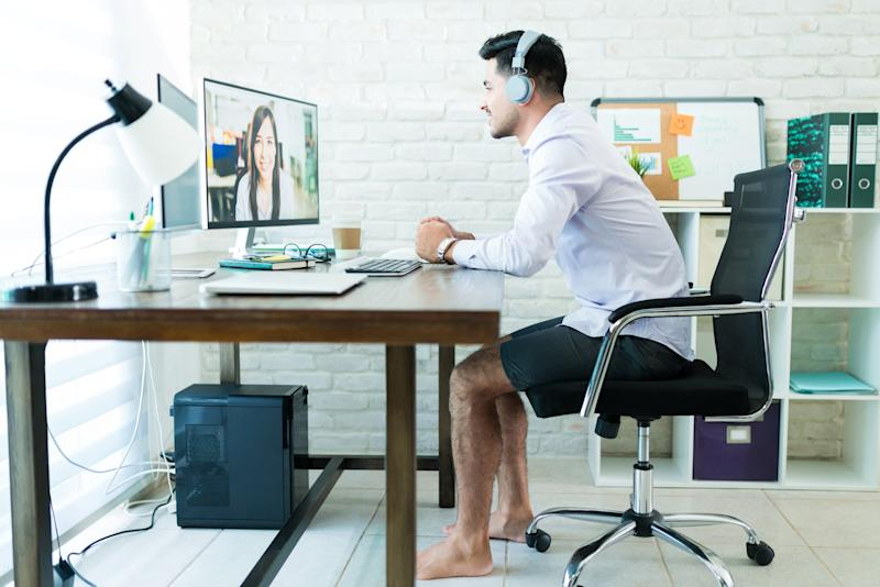 Young businessman taking a conference call barefoot and while wearing shorts comfortably at home