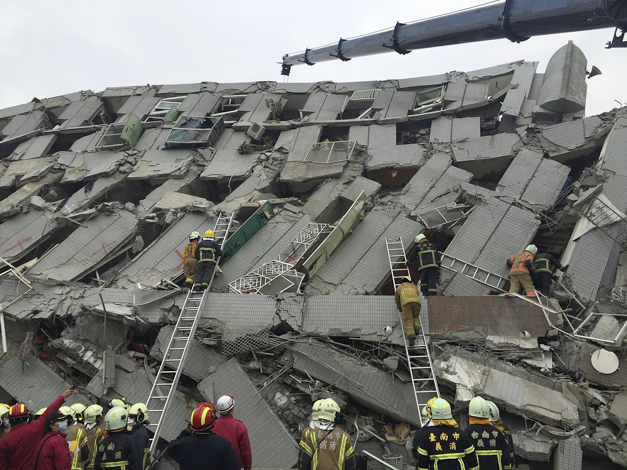 Rescue personnel work at the site where a 17 story apartment building collapsed from an earthquake in Tainan