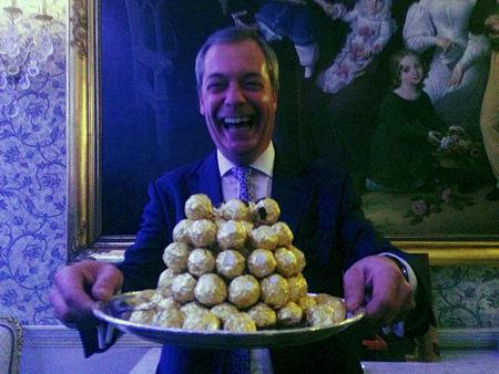 Nigel Farage, the interim leader of the United Kingdom Independence Party (UKIP) holds a platter of Ferrero Rocher chocolates during a party in London