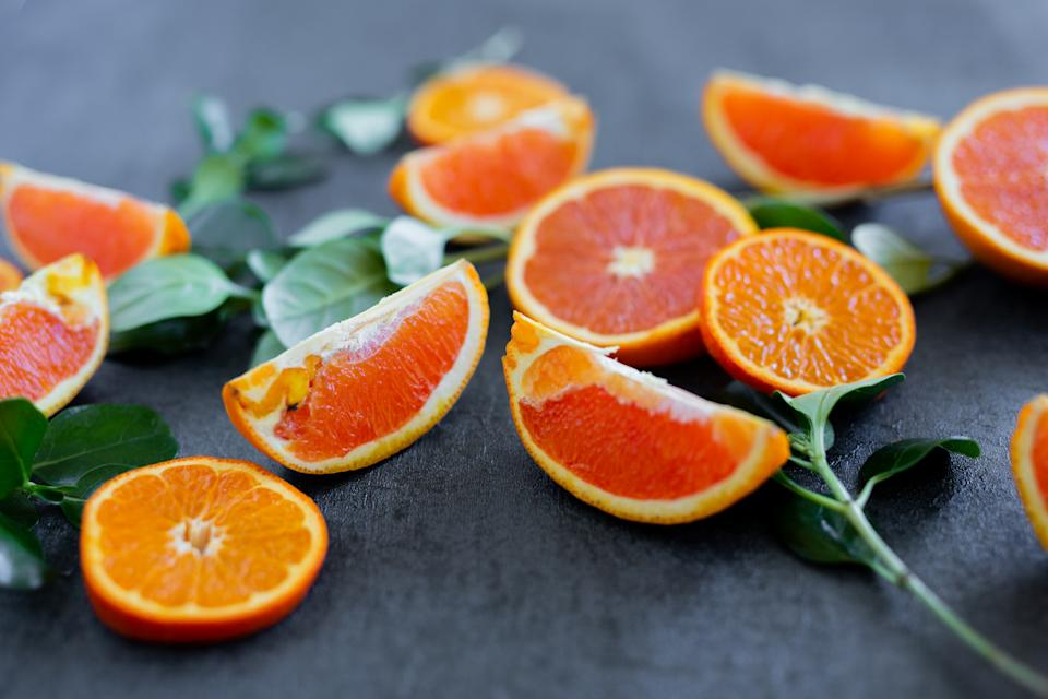 Variety of Fresh Juicy Citrus Fruit Displayed on Platter and Backgrounds with Green Leaves and Negative Space
