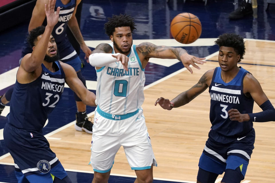 Charlotte Hornets' Miles Bridges (0) gets off a pass from between Minnesota Timberwolves' Karl-Anthony Towns (32) and Jaden McDaniels (3) during the first half of an NBA basketball game Wednesday, March 3, 2021, in Minneapolis. (AP Photo/Jim Mone)