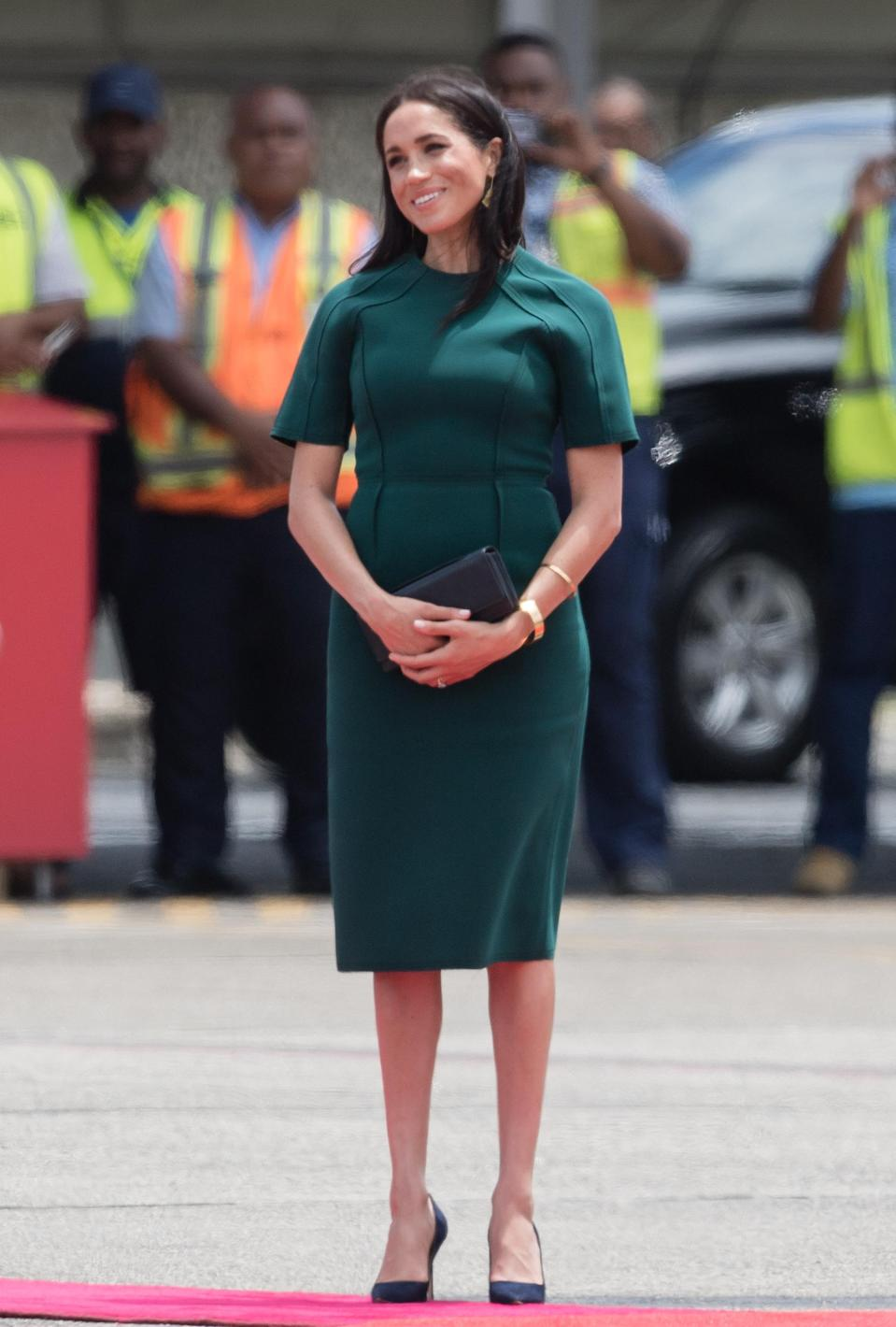 <p>On October 25, the royal couple were welcomed to Nadi airport in Fiji. The Duchess of Sussex was photographed wearing a forest green Jason Wu dress with navy £484 Manolo Blahnik shoes to finish. <em>[Photo: Getty]</em> </p>