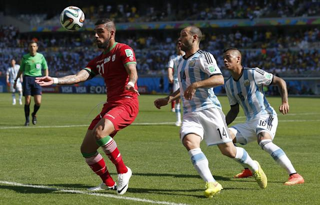 Iran's Ashkan Dejagah, left, shields the ball from Argentina's Javier Mascherano during the group F World Cup soccer match between Argentina and Iran at the Mineirao Stadium in Belo Horizonte, Brazil, Saturday, June 21, 2014. (AP Photo/Jon Super)