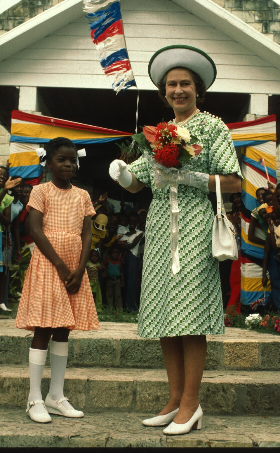 BARBADOS - NOVEMBER 01: Queen Elizabeth ll smiles with a young girl in Barbados on November 01, 1977 in Barbados. (Photo by Anwar Hussein/Getty Images)
