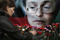 FILE- In this Oct. 7, 2009, file photo, a woman places flowers before a portrait of slain Russian journalist Anna Politkovskaya, in Moscow. Politkovskaya, who won international acclaim for her reporting on the human rights abuses in the Russian republic of Chechnya was shot dead in the elevator of her Moscow apartment building. (AP Photo/Pavel Golovkin, File)
